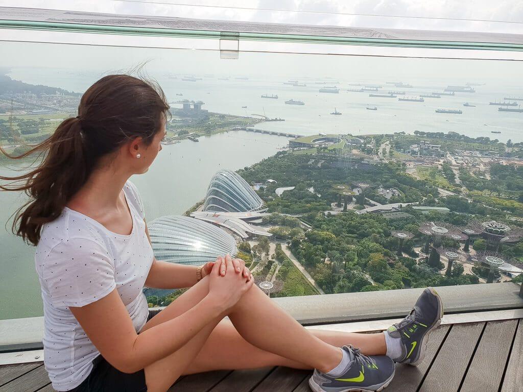Frau sitzt auf Aussichtsdeck und blickt hinunter auf die Gardens by the Bay