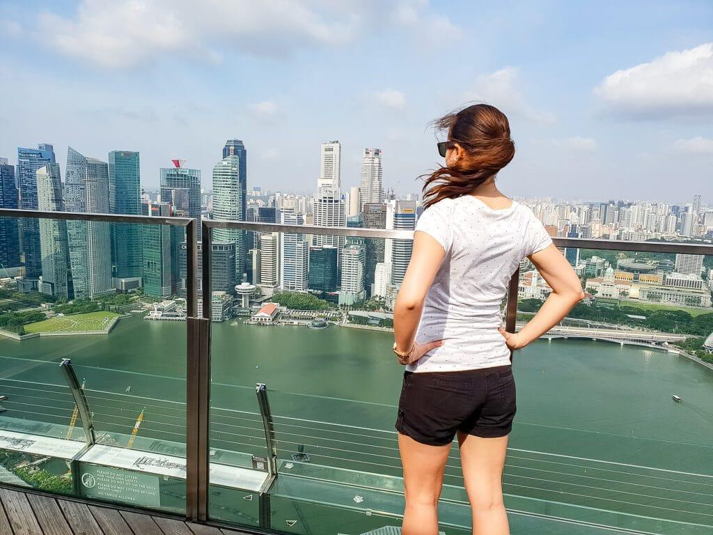 Frau steht im Wind auf Aussichtsplattform und schaut auf die Skyline von Singapur