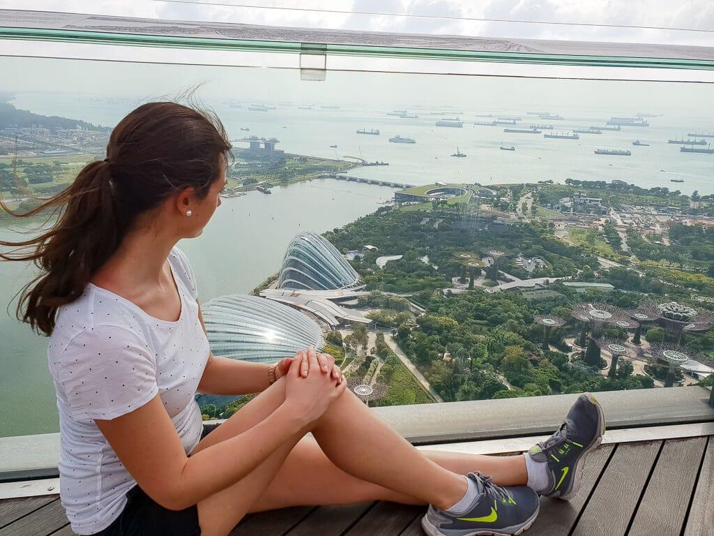 Frau sitzt auf Aussichtspunkt mit Blick auf die Gardens by the Bay