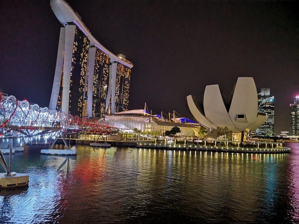 Brücke links, dahinter das Marina Bay Sands bei Nacht - Licht spiegelt auf dem Wasser
