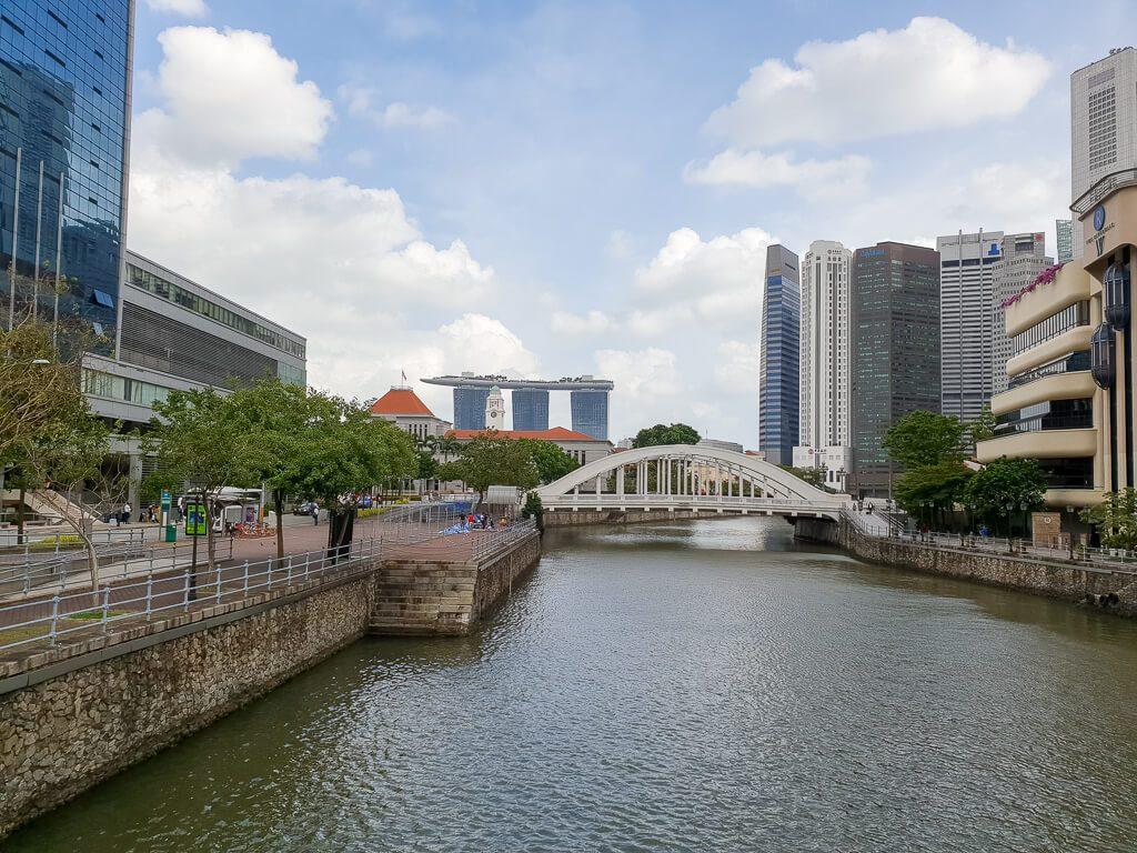 Fluss in der Mitte mit einer weißen Brücke - im Hintergrund das Marina Bay Sands und zu beiden Seiten Hochhäuser