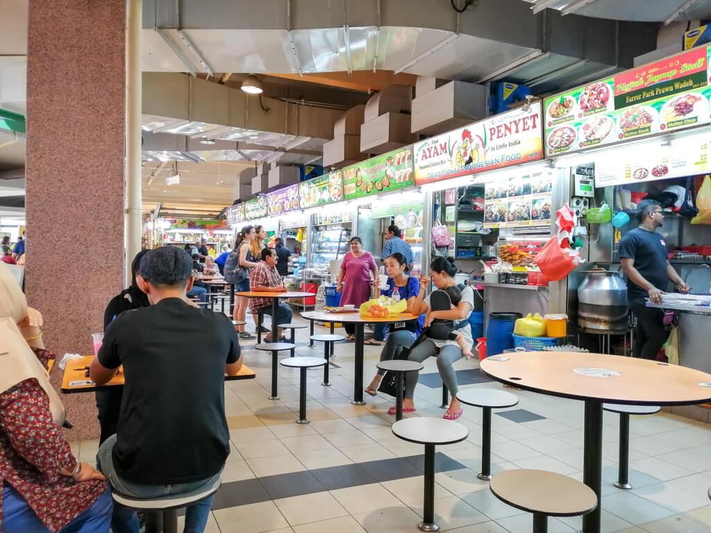 Tekka Centre Singapur - Essensstände an der Seite, in der Mitte Sitzgelegenheiten und einige Menschen