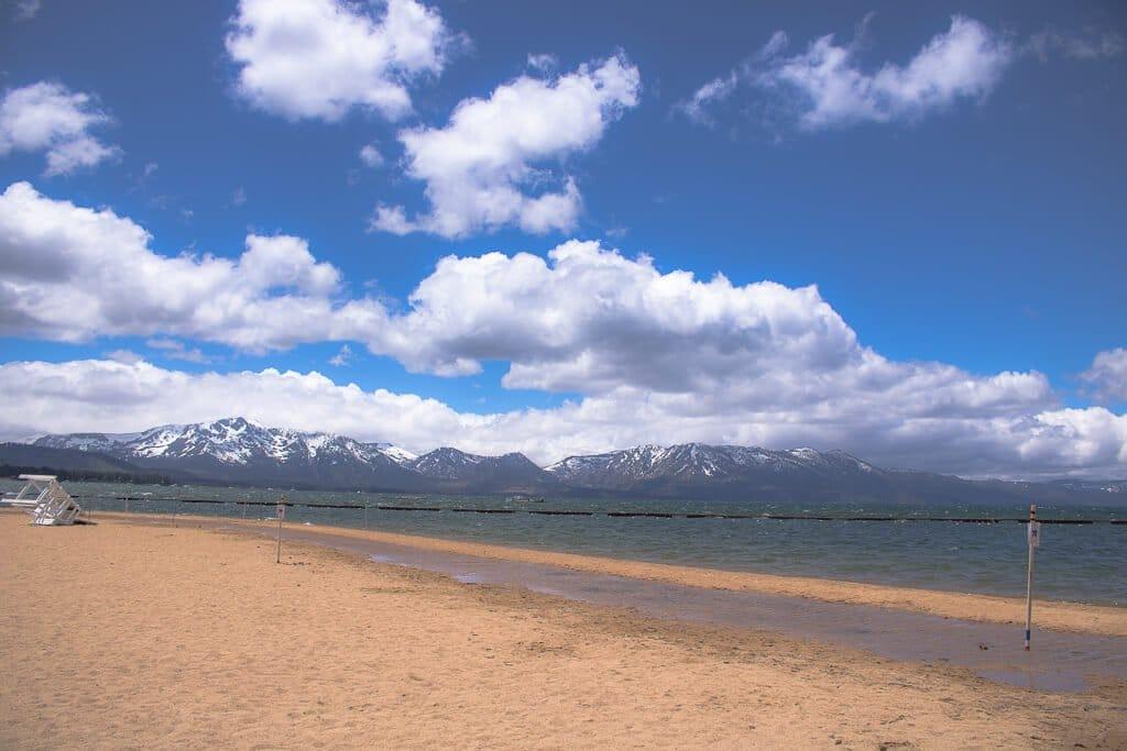 South Lake Tahoe - Strand, See und schneebedeckte Berge im Hintergrund