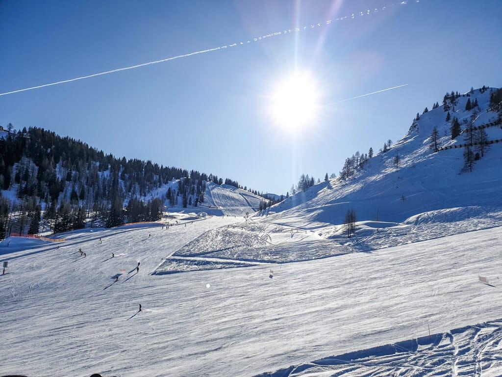 Sonne steht über schneebedeckten Skipisten