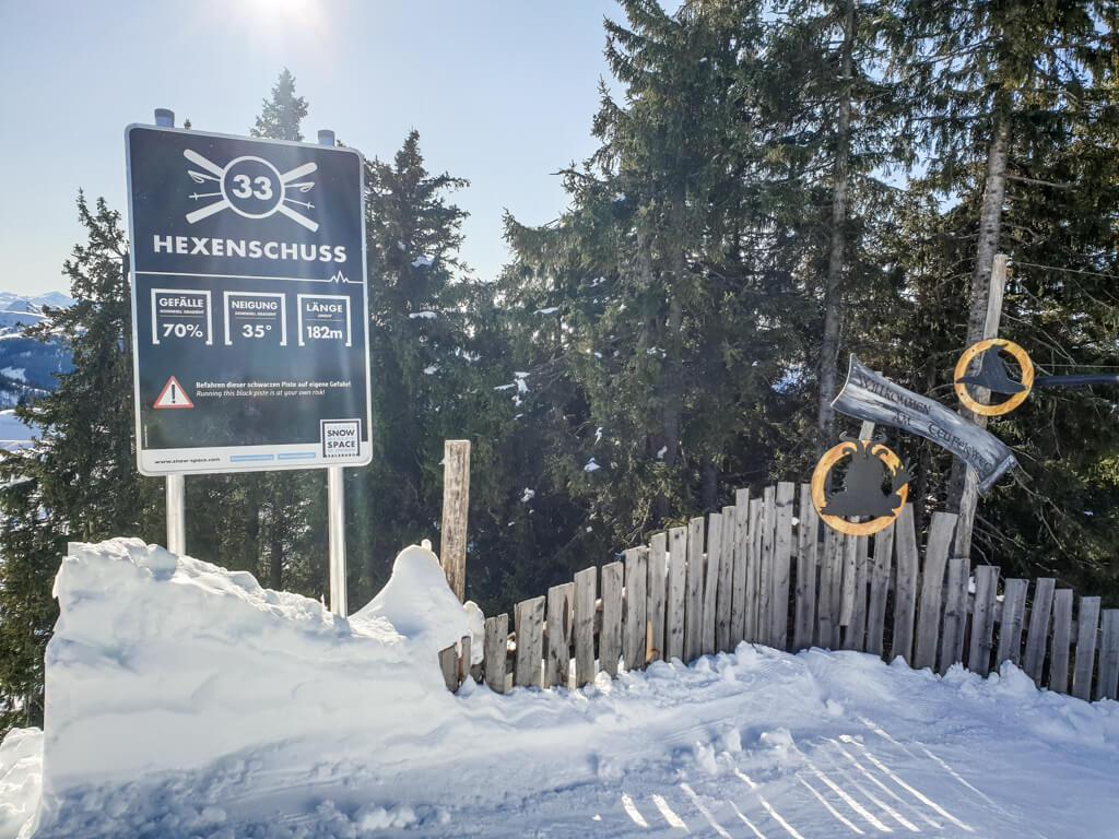 """Schild """"Hexenschuss"""" auf einer schneebedeckten Skipiste"""