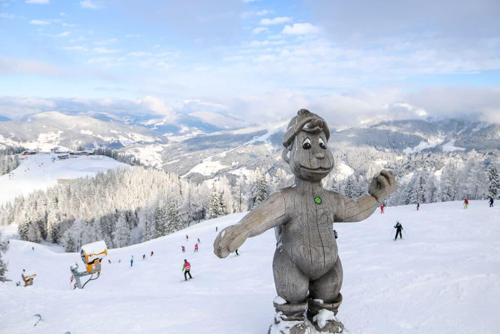 Holzfigur auf einem verschneiten Berg