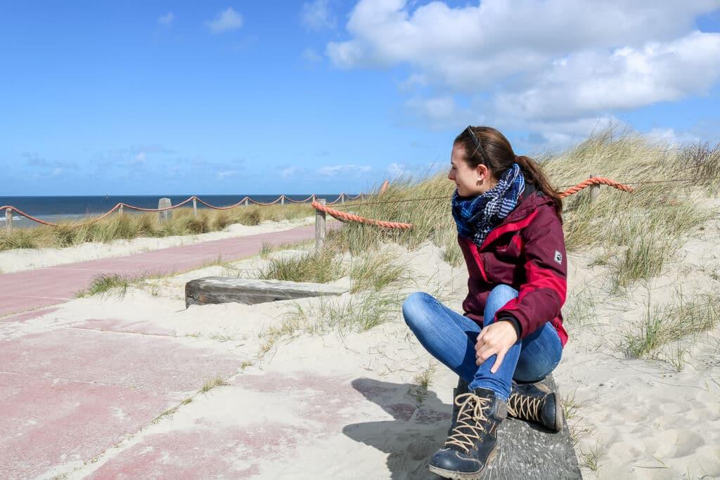 Frau sitzt auf einer Bank in der Sonne an einer Promenade auf Texel - dahinter Sand und Gras