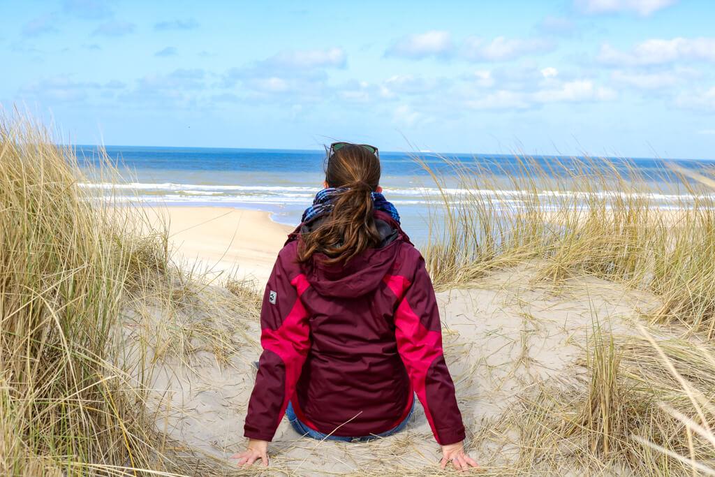 Frau sitzt mit Blick zum Meer auf einer mit Gras bewachsenen Sanddüne