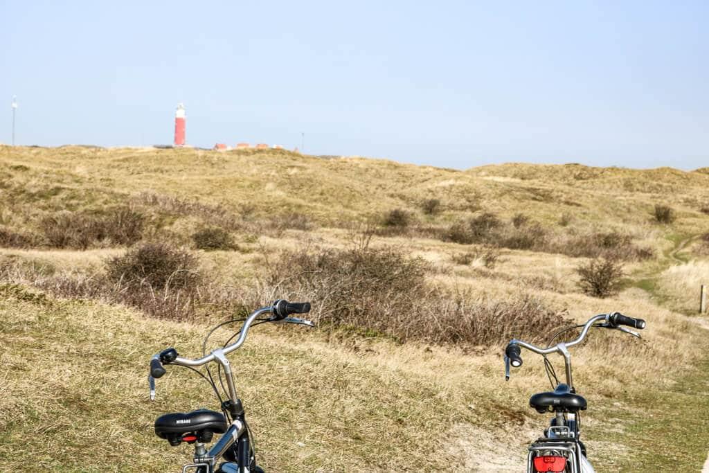 zwei Fahrräder stehen in einer Graslandschaft - im Hintergrund ein roter Leuchtturm