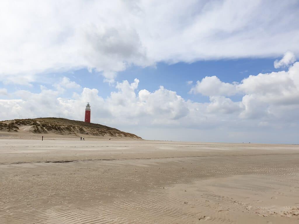 breiter Sandstrand mit Blick auf den Leuchtturm von Texel