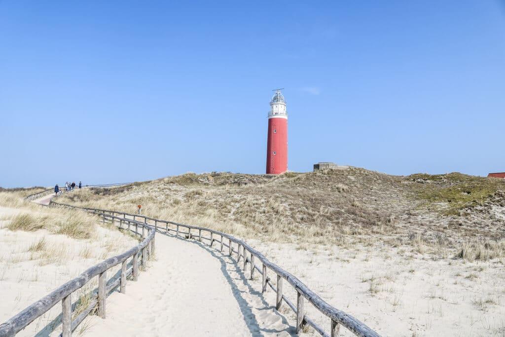 ein sandiger Weg führt zu einem roten Leuchtturm auf einer kleinen Anhöhe