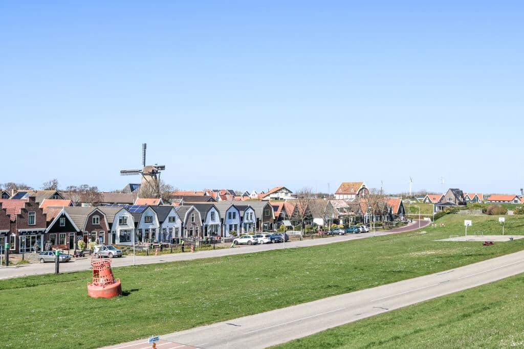Blick auf eine Häuserreihe und eine Windmühle vom Deich aus