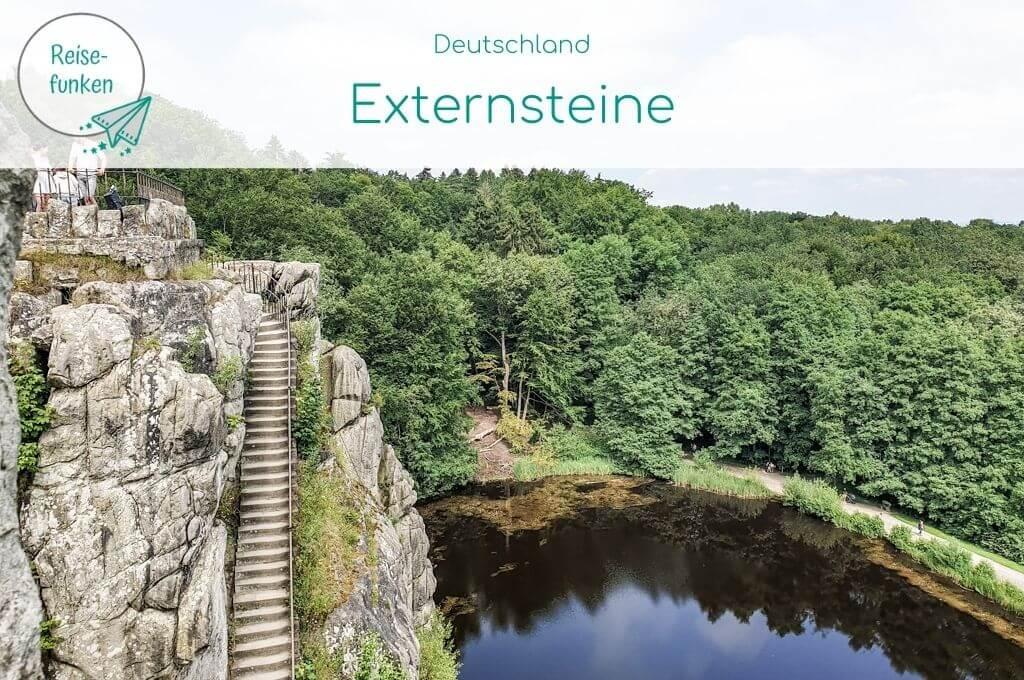 Bild zeigt links Felsen der Externsteine mit Treppe, darunter ist ein Teich zu sehen, in dem sich der Wald spiegelt