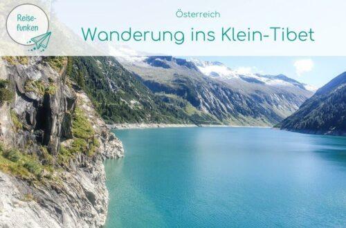 """Bild zeigt blauen Stausee inmitten von Bergen - oben ein Textoverlay: """"Österreich - Wanderung ins Klein-Tibet"""""""