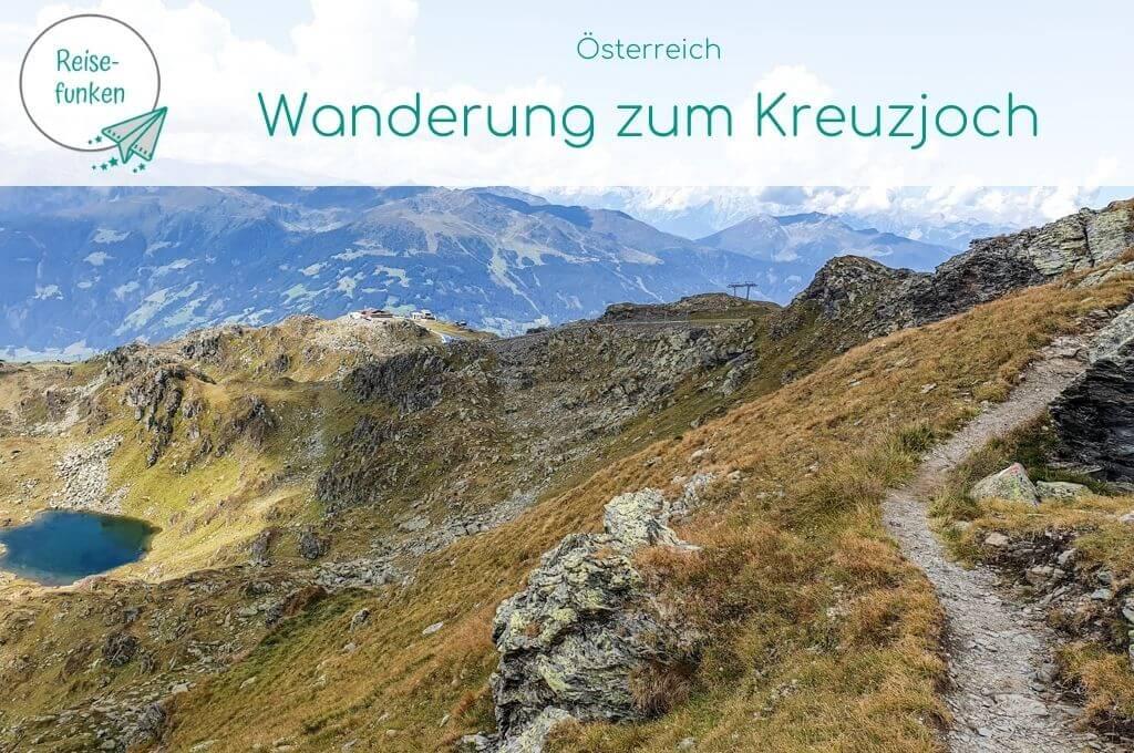 """Titelbild """"Wanderung zum Kreuzjoch"""" - Bild zeigt schmalen Wanderweg in den Bergen, links davon ein blauer Bergsee"""