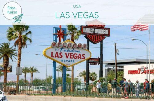 """Bild zeigt das Las Vegas Sign von vorne auf dem Mittelstreifen einer Fahrbahn. Oben über dem Bild liegt ein helles Overlay mit Text """"USA - Las Vegas"""""""
