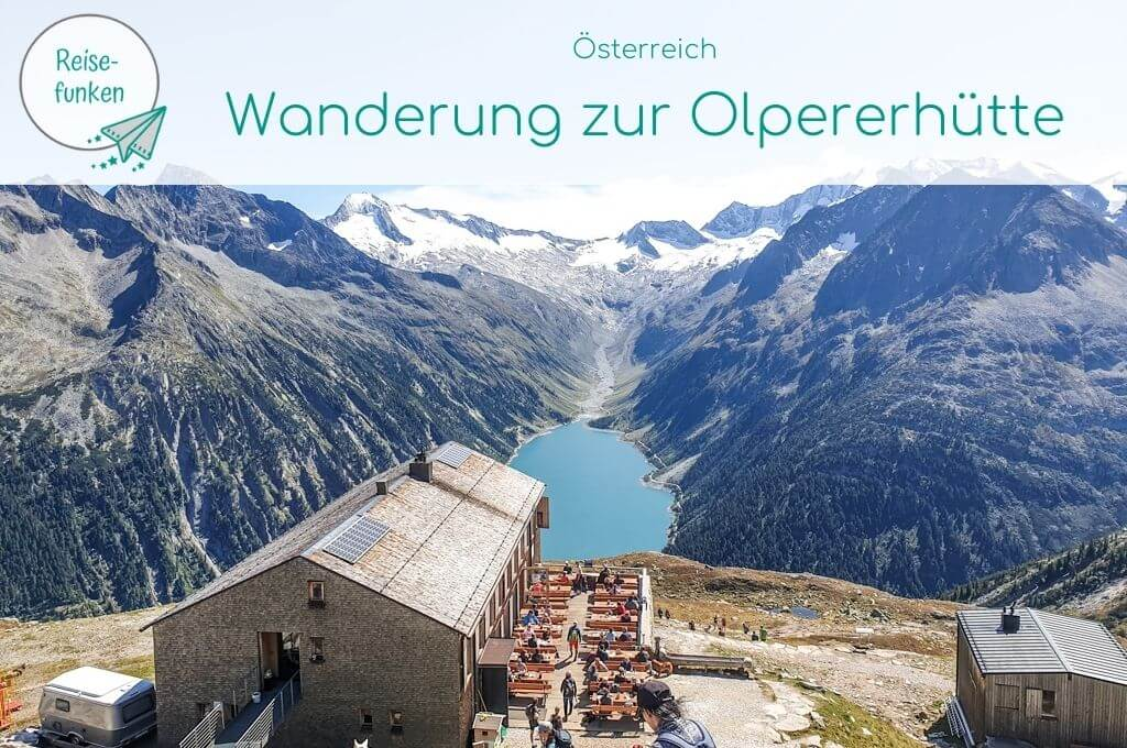 Bild trägt den Titel - Österreich - Wanderung zur Olpererhütte. Bild zeigt eine Hütte in den Bergen mit Ausblick auf einen Stausee
