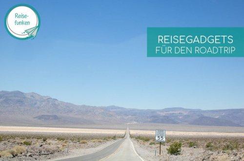 Straße im Death Valley - Wüste zu beiden Seiten, dahinter eine Gebirgskette