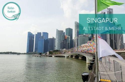 Brücke mit Fahnen, links Wasser und im Hintergrund die Skyline von Singapur