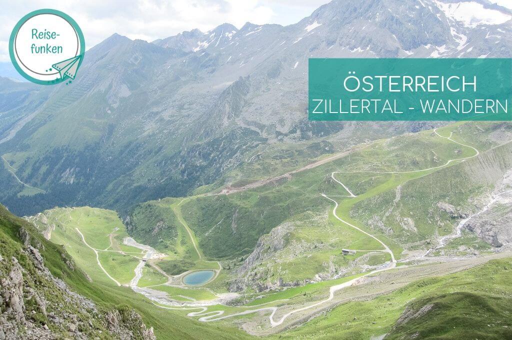 Bergsee umgeben von Wegen und grünen Bergen