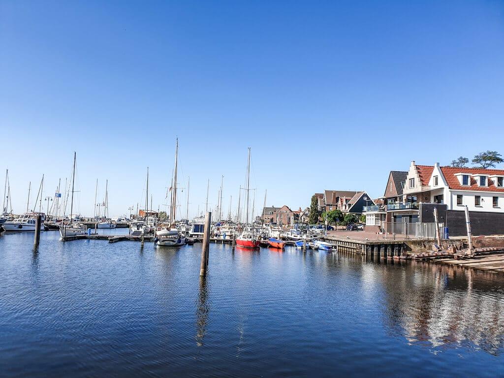 Segelboote liegen im Hafen und spiegeln sich im Wasser