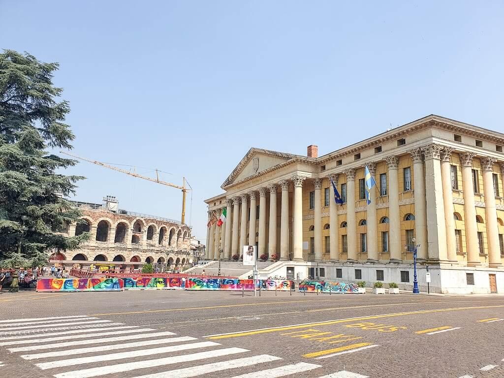 Rathaus mit Säulen - im Vordergrund eine Straße - im Hintergrund die Arena di Verona