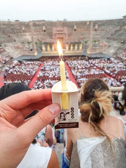 Hand mit Kerze im Vordergrund - dahinter die Arena di Verona
