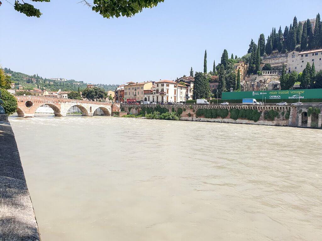 Verona - Fluss Etsch, im Hintergrund eine Brücke und rechts Hügel mit Gebäuden