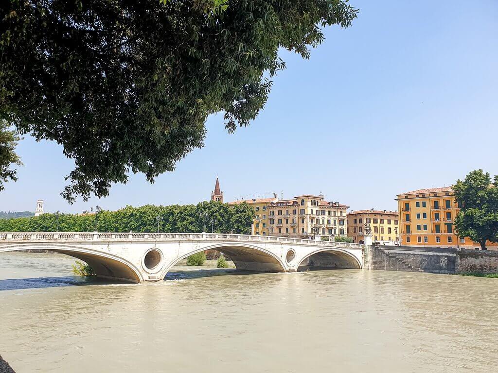 Brücke über den Fluss Etsch in Verona; im Hintergrund Häuser