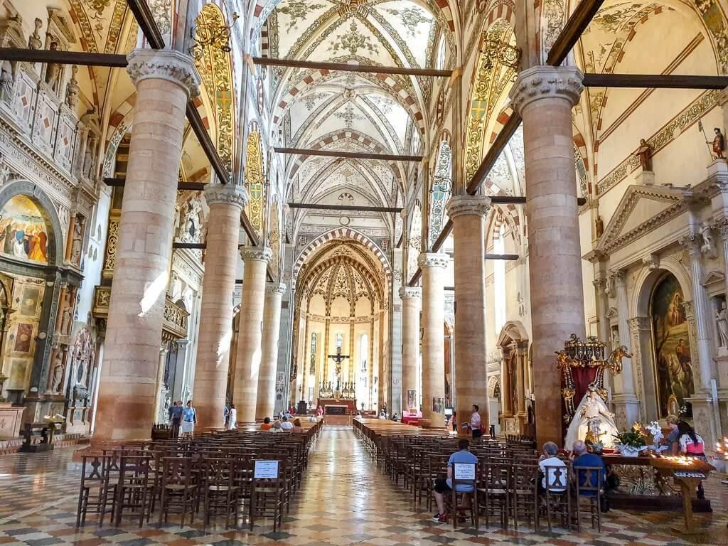 Innenraum einer Kirche mit hohen Säulen und Bänken