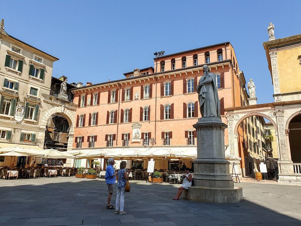 Platz umgeben von farbigen Gebäuden, in der Mitte steht eine Statue