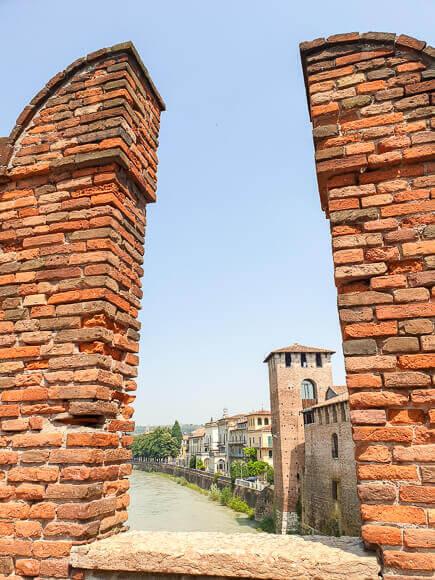 Blick zwischen zwei Brückenpfeilern mit Sicht auf Fluss und Burg