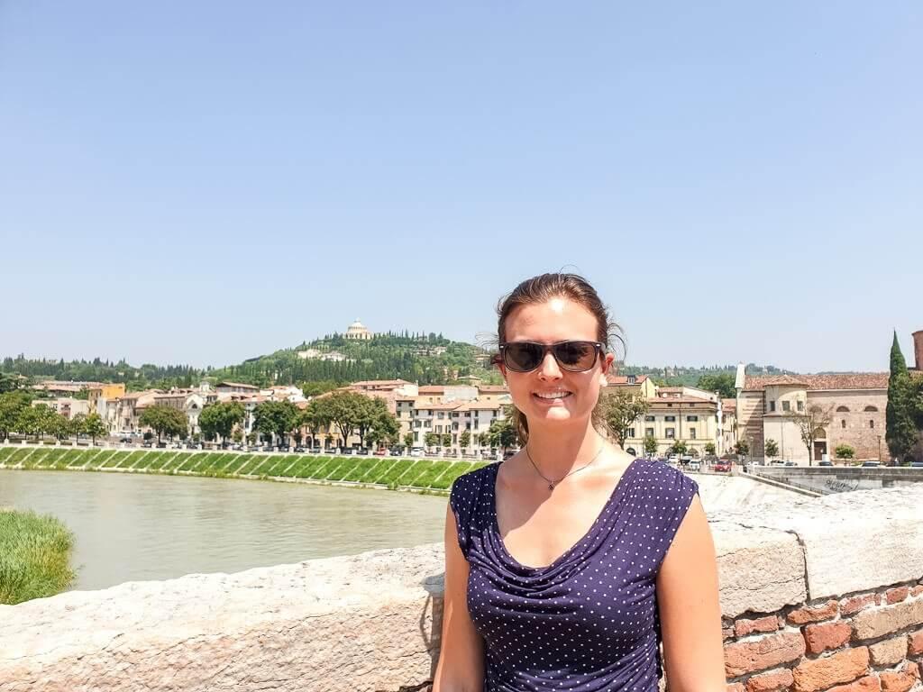 Frau steht auf Brücke - Fluss im Hintergrund