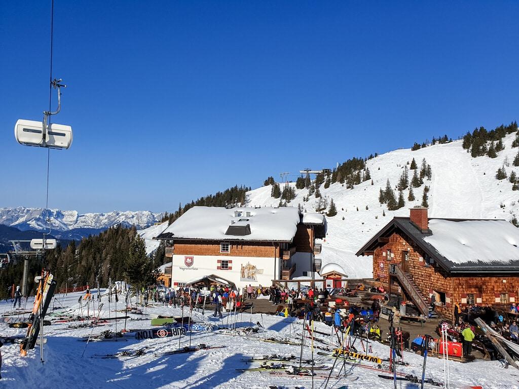 zwei Häuser in den Bergen, davor viele abgestellte Skier