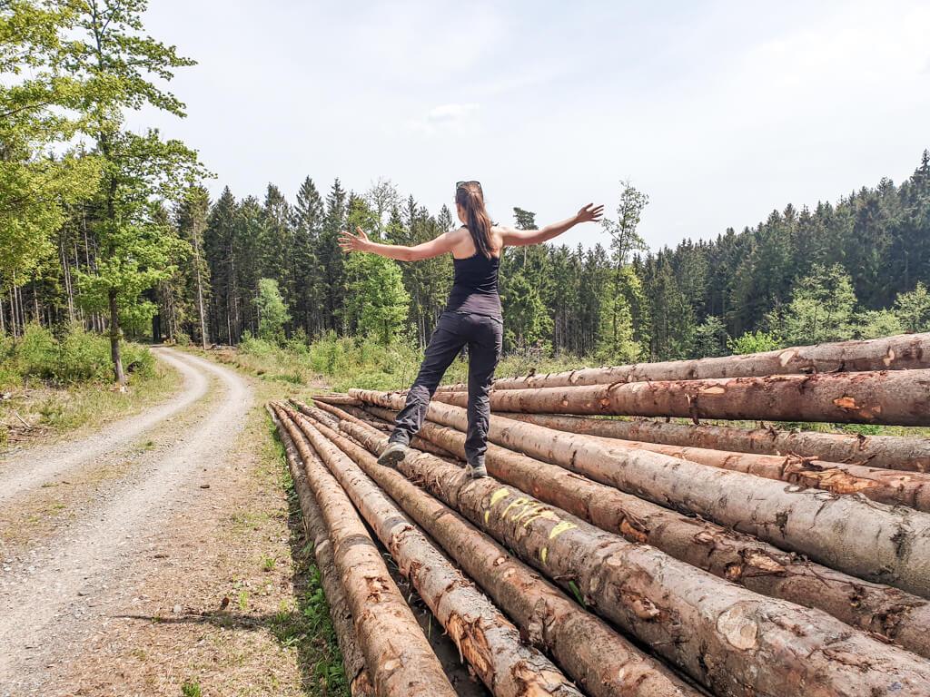 Frau balanciert auf einem Holzstapel im Wald