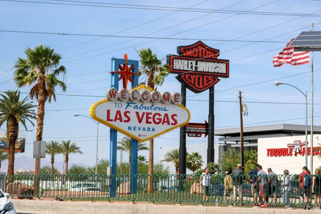 """Las Vegas Sign mit Aufschrift """"Welcome to fabulous Las Vegas""""; Schild ist umgeben von wenigen, hohen Palmen am Rande der Straße"""