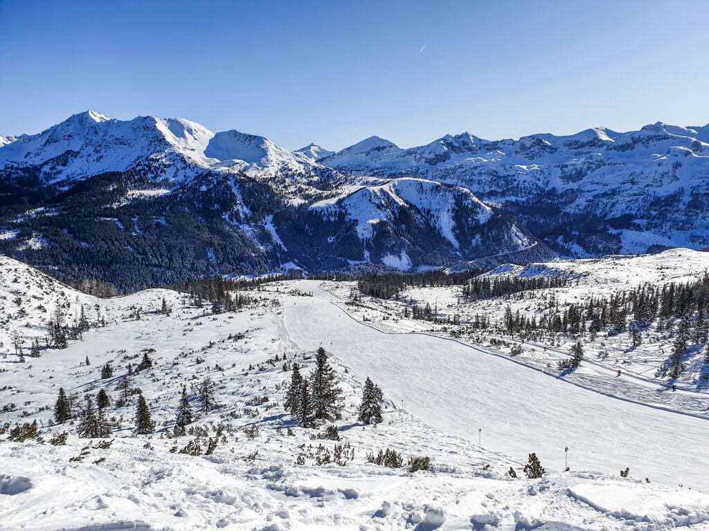 Blick auf eine Skipiste inmitten von schneebedeckten Bergen