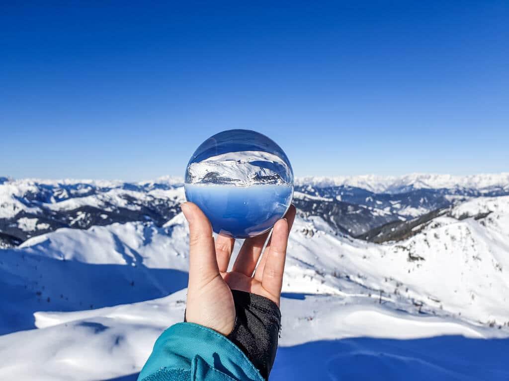Hand hält Glaskugel in der sich das Bergpanorama spiegelt