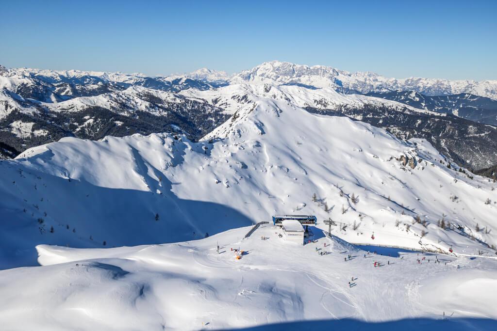 Aussicht auf ein schneebedecktes Plateau mit Gondelstation - im Hintergrund Berge