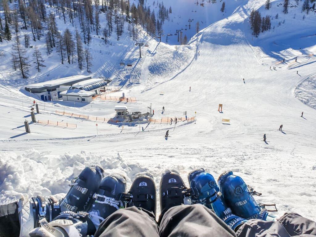 3 Beine mit Skischuhen vor einem Ausblick auf die Skipiste
