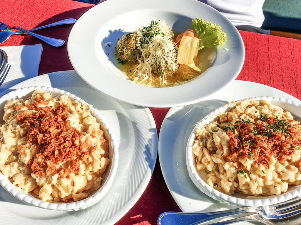 zwei Portionen Käsespätzle und Spinatknödel auf einem Tisch
