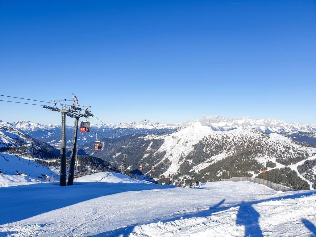 Gondelbahn links, daneben und dahinter schneebedeckte Berge