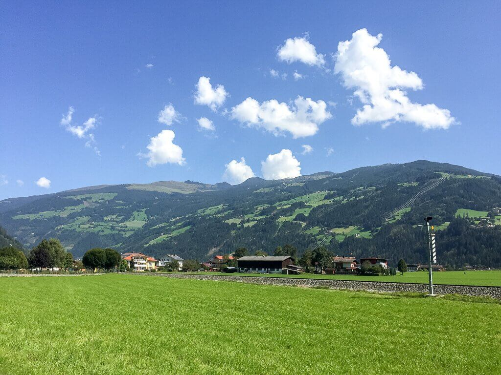 im Hintergrund bewaldete Berge, davor eine grüne Wiese und Bahngleise