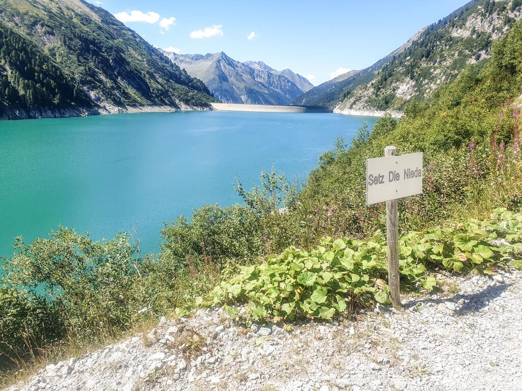 """Blick auf einen blauen Bergsee umgeben von Bergen. Im Vordergrund steht ein Schild """"Setz die Nieda""""."""