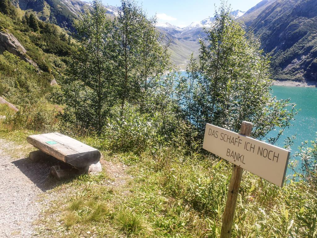 """kleine Holzbank mit Schild """"Das Schaff ich noch Bankl"""" im Grünen, dahinter ein blauer Bergsee"""