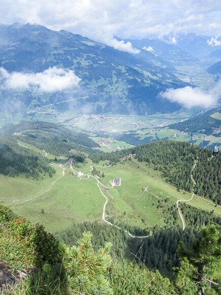 Ausblick auf grüne Wiesen und Berge mit einigen Wolken