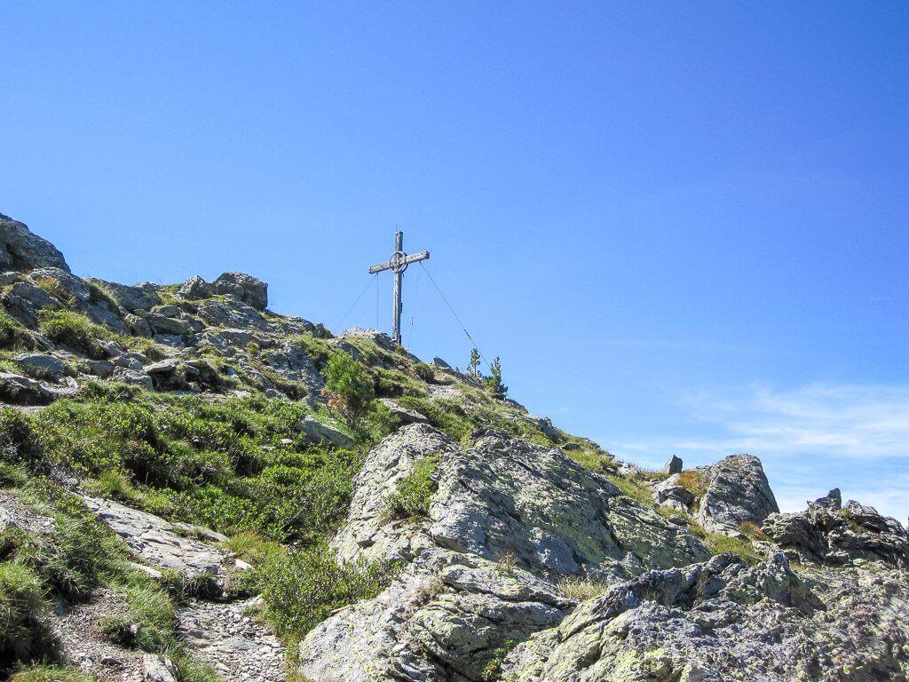 Gipfelkreuz auf einem felsigen Berggipfel