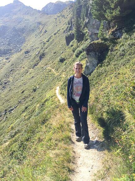 Frau steht auf schmalem Wanderweg in den Bergen