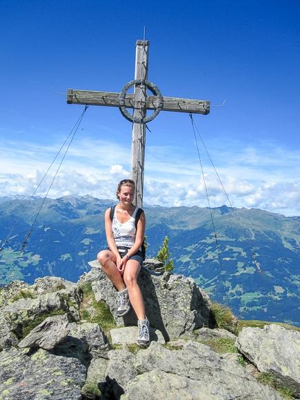 Frau sitzt vor Gipfelkreuz - im Hintergrund das Tal