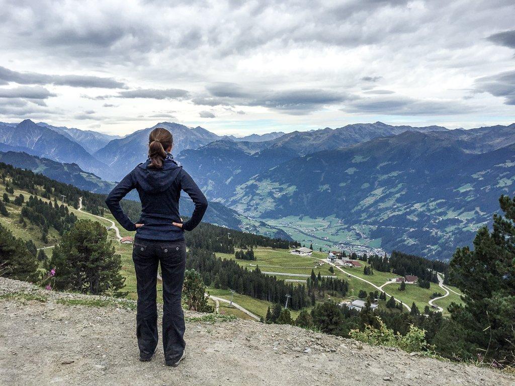 Frau steht am Rand eines Abgrundes - dahinter sind grüne Berge zu sehen